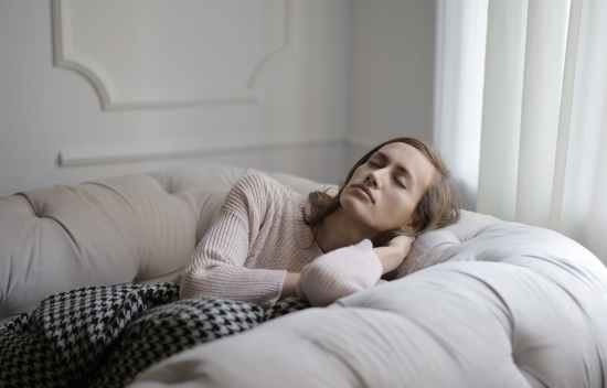 girl in white sweater lying on couch